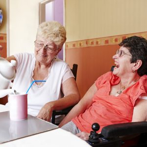 Two women laughing. One woman is pouring tea into a mug with a straw for the other woman, who is in a motorised wheelchair.