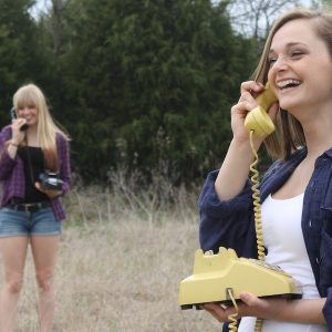 Two young women smiling and talking on old-fashioned rotary phones while standing outside